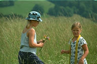 Girls in hay meadow with flowers and panama hat