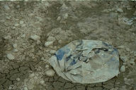 worn plastic bag on the bottom of a dried up pond